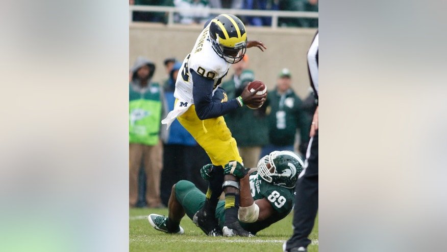 Michigan State's Shilique Calhoun (89) sacks Michigan quarterback Devin Gardner during the first quarter of an NCAA college football game, Saturday, Nov. 2, 2013, in East Lansing, Mich. Michigan State won 29-6. (AP Photo/Al Goldis)
