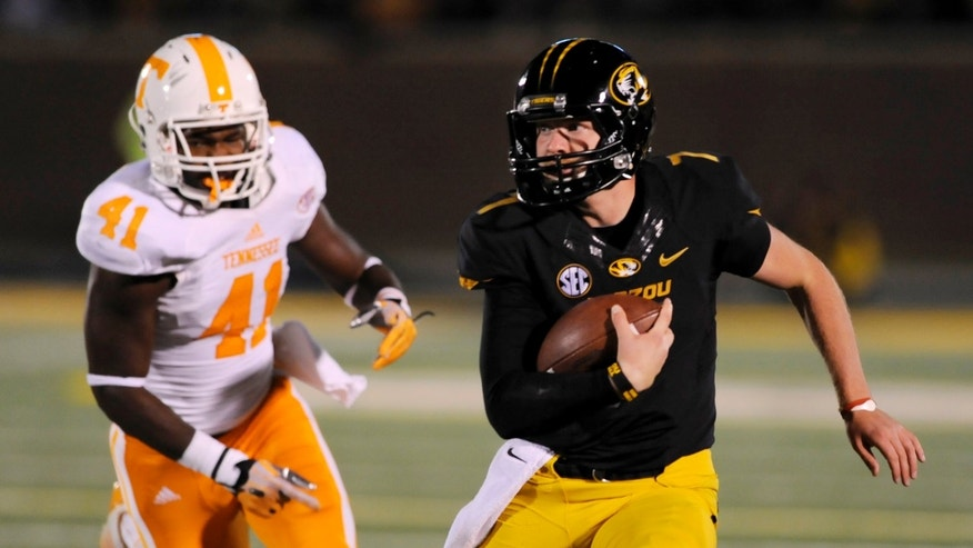 Missouri quarterback Maty Mauk, right, runs for a 19-yard gain past Tennessee linebacker Dontavis Sapp during the first half of an NCAA college football game Saturday, Nov. 2, 2013, in Columbia, Mo. (AP Photo/L.G. Patterson)