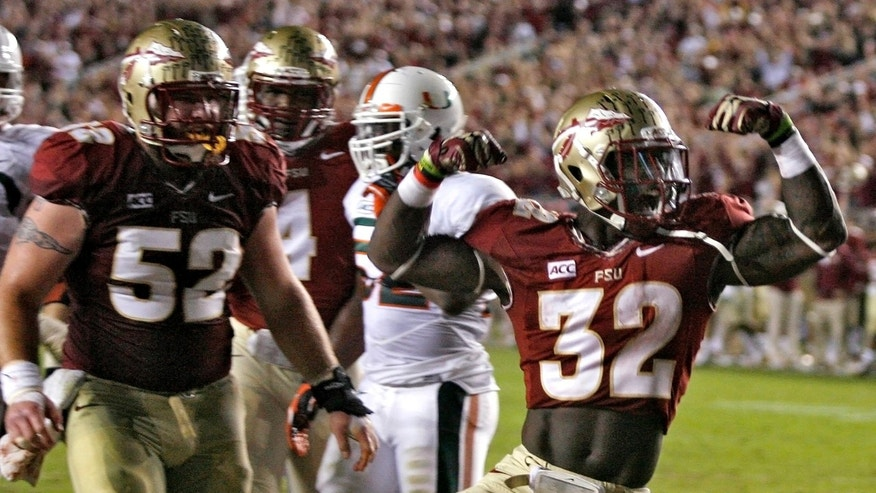 Florida State running back James Wilder Jr. (32) celebrates after scoring a touchdown against Miami during the second quarter of an NCAA college football game Saturday, Nov. 2, 2013, in Tallahassee, Fla. At left is lineman Bryan Stork (52). (AP Photo/Phil Sears)