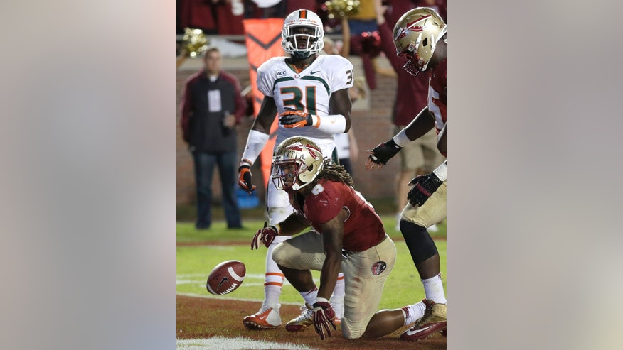 Florida State running back Devonta Freeman (8) flips the ball after scoring past Miami linebacker Tyrone Cornileus (31) on a 5-yard touchdown run during the first quarter of an NCAA college football game Saturday, Nov. 2, 2013, in Tallahassee, Fla. (AP Photo/Chris O'Meara)