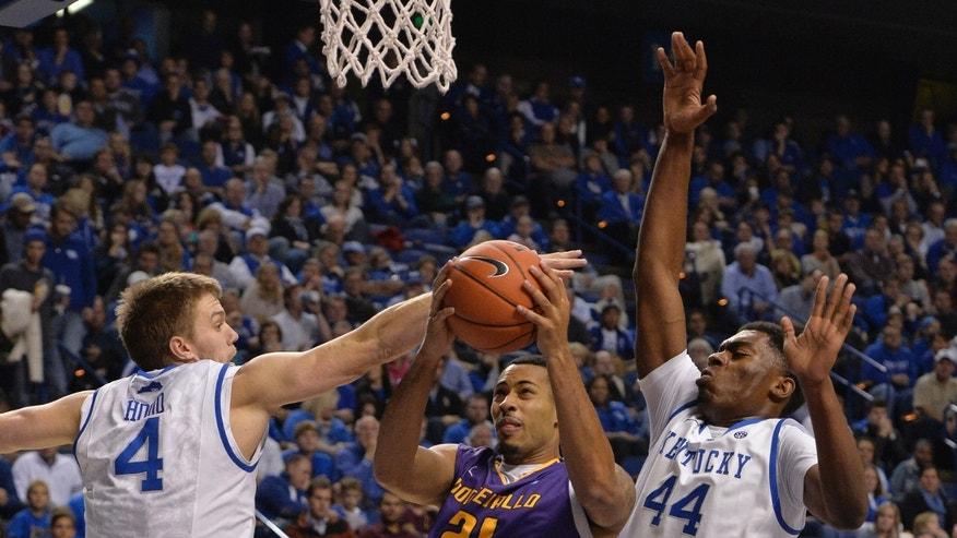 Kentucky's Jon Hood, left, and Dakari Johnson, right, apply defensive pressure to Montevallo's Silas Mills during the first half of an exhibition NCAA basketball game, Friday, Nov. 4, 2013, in Lexington, Ky.  (AP Photo/Timothy D. Easley)