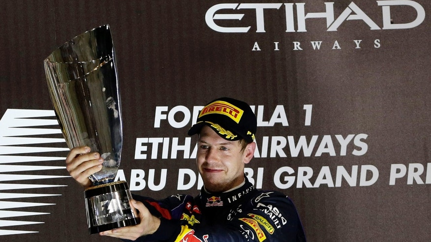 Red Bull driver Sebastian Vettel of Germany holds up the trophy on the podium after winning the Abu Dhabi Formula One Grand Prix at the Yas Marina racetrack in Abu Dhabi, United Arab Emirates, Sunday, Nov. 3, 2013. World champion Sebastian Vettel won the Abu Dhabi Grand Prix in dominant fashion Sunday to clinch a seventh straight victory and 11th of a dominating season.  (AP Photo/Hassan Ammar)