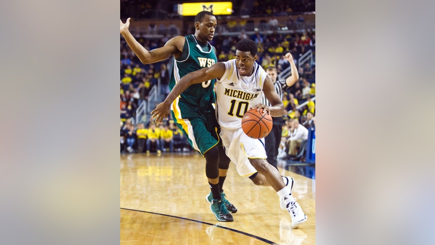 Wayne State guard Chene Phillips, left, defends Michigan guard Derrick Walton Jr. (10) in the first half of an NCAA college basketball exhibition game, at Crisler Center in Ann Arbor, Mich., Monday, Nov. 4, 2013. (AP Photo/Tony Ding)