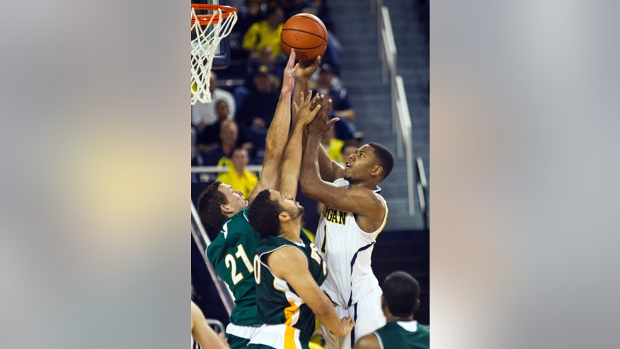 Michigan forward Glenn Robinson III, right, shoots over Wayne State forward John Williamson (21) and forward Michael Lewis (20), in the second half of an NCAA college basketball exhibition game, at Crisler Center in Ann Arbor, Mich., Monday, Nov. 4, 2013. Michigan won 79-60. (AP Photo/Tony Ding)