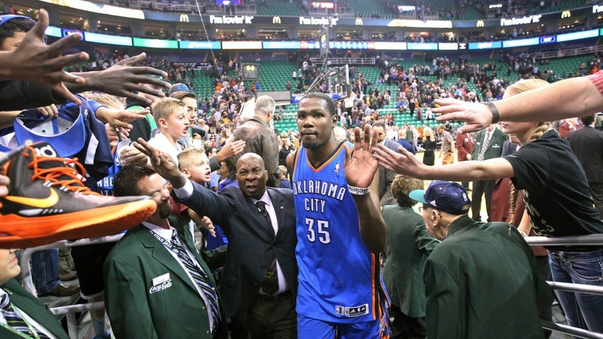 Fans reach for Oklahoma City Thunder's Kevin Durant (35) following an NBA basketball game against the Utah Jazz, Wednesday, Oct. 30, 2013, in Salt Lake City. The Thunder won 101-98. (AP Photo/Rick Bowmer)