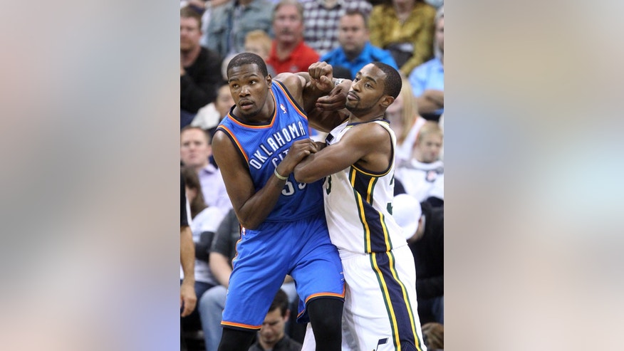 Utah Jazz's Mike Harris, right, battles for position with Oklahoma City Thunder's Kevin Durant in the first half of an NBA basketball game Wednesday, Oct. 30, 2013, in Salt Lake City. (AP Photo/Rick Bowmer)
