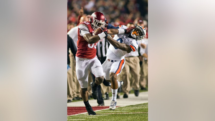 Arkansas safety Korliss Marshall, left, and Auburn defensive back Jonathon Mincy tangle on a Marshall carry during the second half of an NCAA college football game in Fayetteville, Ark., Saturday, Nov. 2, 2013. Auburn won 35-17.  (AP Photo/Beth Hall)