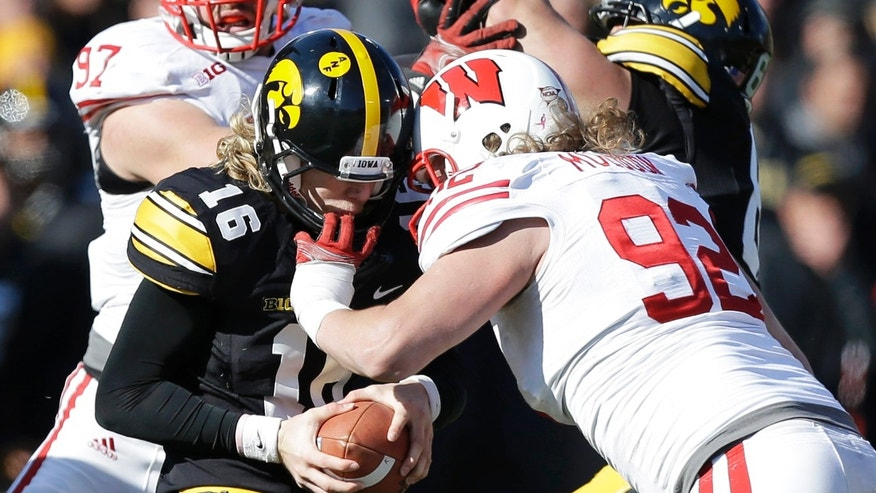 Iowa quarterback C.J. Beathard (16) is sacked by Wisconsin defensive end Pat Muldoon during the second half of an NCAA college football game, Saturday, Nov. 2, 2013, in Iowa City, Iowa. Wisconsin won 28-9. (AP Photo/Charlie Neibergall)