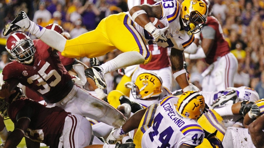 FILE - In this Nov. 3, 2012 file photo, LSU running back Jeremy Hill (33) dives into the end zone for a touchdown against Alabama in the third quarter of an NCAA college football game in Baton Rouge, La., Saturday, Nov. 3, 2012. Hill's 107-yard, one-touchdown performance against Alabama a year ago gave the college football world a sense of how good the LSU running back could be. Yet Hill dwells on opportunities he missed in that game to prevent the eventual national champs from rallying to beat the Tigers. Now Hill aims for redemption this Saturday, Nov. 9, 2013, in Tuscaloosa. (AP Photo/Bill Haber, File)