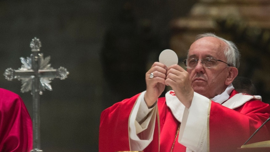 Pope Francis holds up the Host as he celebrates a Mass for cardinals and bishops who died in the past year, in St. Peter's Basilica at the Vatican, Monday, Nov. 4, 2013.  (AP Photo/Andrew Medichini)