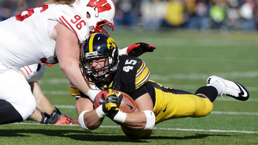 Iowa running back Mark Weisman dives for yardage as he is tackled by Wisconsin nose tackle Beau Allen, left, during the first half of an NCAA college football game, Saturday, Nov. 2, 2013, in Iowa City, Iowa. (AP Photo/Charlie Neibergall)