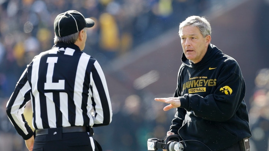 Iowa head coach Kirk Ferentz, right, talks to the line judge during the first half of an NCAA college football game against Wisconsin, Saturday, Nov. 2, 2013, in Iowa City, Iowa. Wisconsin won 28-9. (AP Photo/Charlie Neibergall)