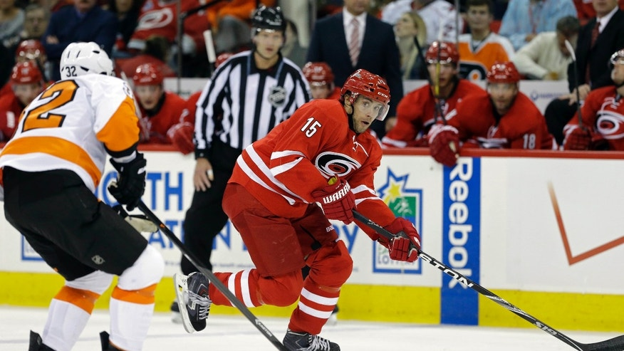 Carolina Hurricanes' Tuomo Ruutu (15), of Finland, controls the puck against Philadelphia Flyers' Mark Streit (32), of Switzerland, during the second period of an NHL hockey game in Raleigh, N.C., Tuesday, Nov. 5, 2013. (AP Photo/Gerry Broome)