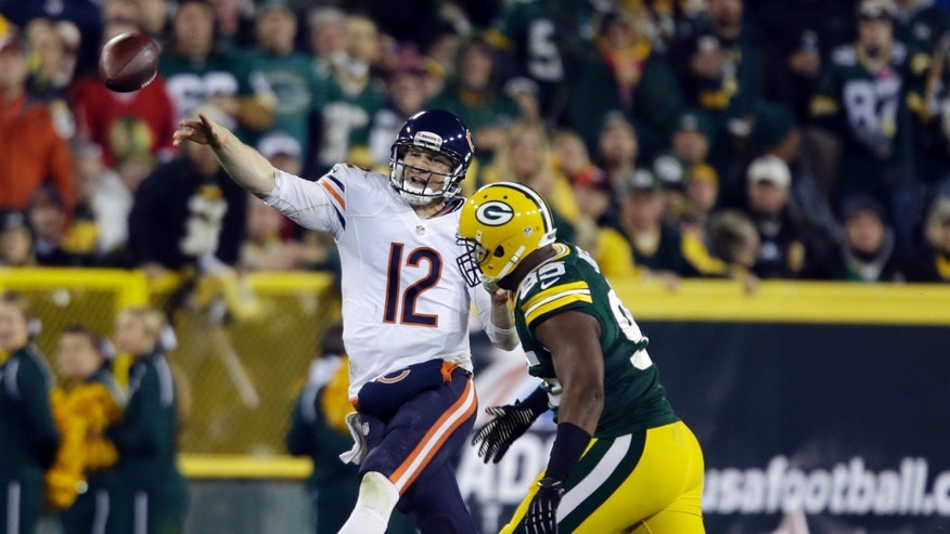 Chicago Bears quarterback Josh McCown throws past Green Bay Packers' Datone Jones during the second half of an NFL football game Monday, Nov. 4, 2013, in Green Bay, Wis. (AP Photo/Jeffrey Phelps)
