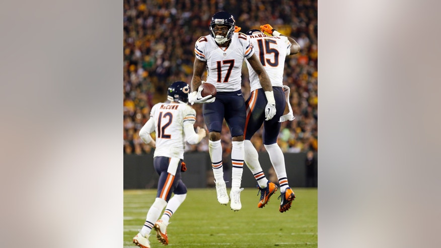 Chicago Bears' Brandon Marshall (15) celebrates one of his touchdown catches with teammates Alshon Jeffery (17) and Josh McCown (12) during the second half of an NFL football game against the Green Bay Packers Monday, Nov. 4, 2013, in Green Bay, Wis. (AP Photo/Jeffrey Phelps)