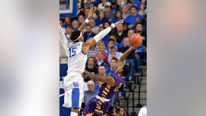 Montevallo's Troran Brown, right, attempts an off balance shot through the defense of Kentucky's Willie Cauley-Stein during the second half of an exhibition NCAA basketball game, Friday, Nov. 4, 2013, in Lexington, Ky. Kentucky defeated Montevallo 95-72.  (AP Photo/Timothy D. Easley)