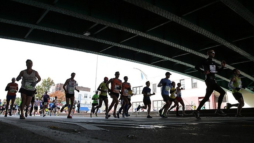 Nov. 3, 2013: Runners pass under a bridge on Fourth Avenue in the Brooklyn borough of New York during the New York City Marathon. (AP/Peter Morgan)