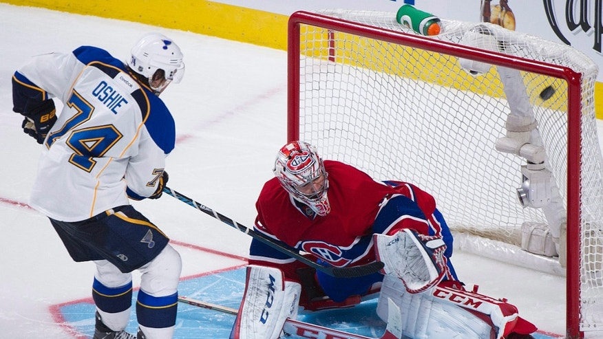 St. Louis Blues' T.J. Oshie scores on Montreal Canadiens goalie Carey Price during the shootout in an NHL hockey game in Montreal, Tuesday, Nov. 5, 2013. (AP Photo/The Canadian Press, Graham Hughes)