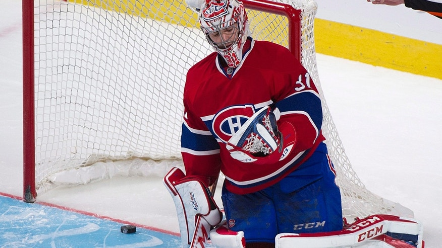 Montreal Canadiens goaltender Carey Price kneels in the crease after being scored on by St. Louis Blues' T.J. Oshie during the shootout in an NHL hockey game in Montreal, Tuesday, Nov. 5, 2013. (AP Photo/The Canadian Press, Graham Hughes)