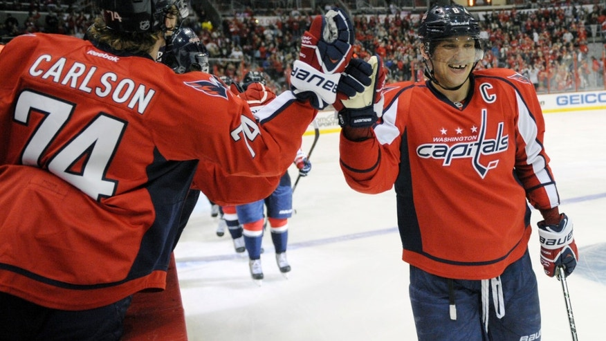 Washington Capitals right wing Alex Ovechkin (8), of Russia, celebrates his goal with John Carlson against the New York Islanders during the second period an NHL hockey game, Tuesday, Nov. 5, 2013, in Washington. (AP Photo/Nick Wass)