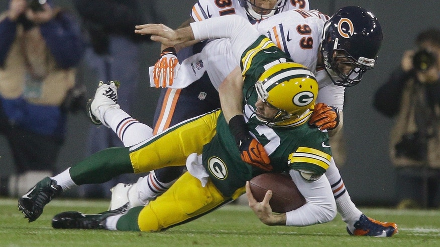 Green Bay Packers quarterback Aaron Rodgers is sacked by Chicago Bears' Shea McClellin (99) and Isaiah Frey (31) during the first half of an NFL football game Monday, Nov. 4, 2013, in Green Bay, Wis. Rodgers left the game after the play. (AP Photo/Jeffrey Phelps)