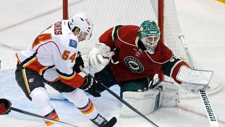 Minnesota Wild goalie Josh Harding, right, stops a scoring threat by Calgary Flames' David Jones in the third period of an NHL hockey game, Tuesday, Nov. 5, 2013 in St. Paul, Minn. The Wild won 5-1. (AP Photo/Jim Mone)