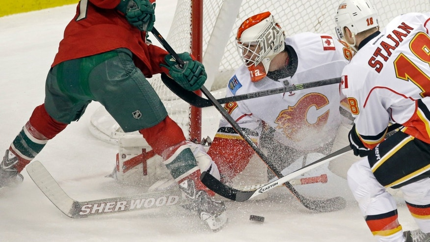 Minnesota Wild's Zach Parise, left, is thwarted in his attempt to score by Calgary Flames goalie Reto Berra in the first period of an NHL hockey game, Tuesday, Nov. 5, 2013, in St. Paul, Minn. (AP Photo/Jim Mone)