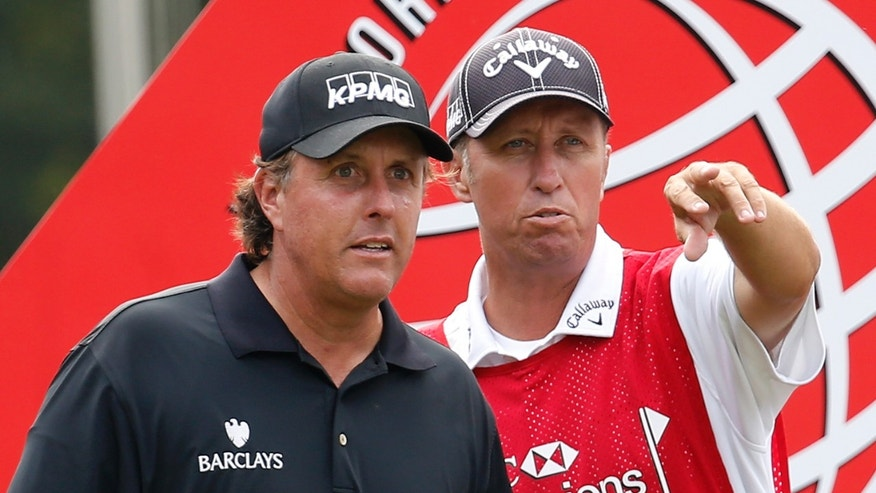 Phil Mickelson of the United States, left, listens to his caddie before tying off the 10th hole during the second round of the HSBC Champions golf tournament at the Sheshan International Golf Club in Shanghai, China, Friday, Nov. 1, 2013. (AP Photo/Eugene Hoshiko)