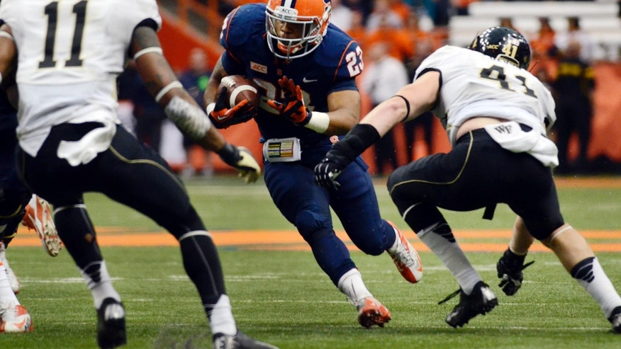 Syracuse's Prince-Tyson Gulley, center, attempts to run past Wake Forest's Anthony Wooding, Jr., left, and Mike Olson during an NCAA college football game at the Carrier Dome in Syracuse, N.Y., Saturday, Nov. 2, 2013. (AP Photo/Heather Ainsworth)