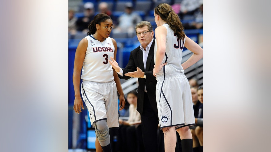 Connecticut coach Geno Auriemma, center talks with players Morgan Tuck, left, and Breanna Stewart during the first half of an NCAA college exhibition basketball game against Philadelphia, Tuesday, Nov. 5, 2013, in Hartford, Conn. (AP Photo/Jessica Hill)