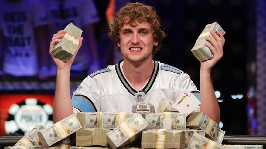 Nov. 5, 2013: Ryan Riess holds up two bricks of $100 bills after winning the World Series of Poker Final Table in Las Vegas. Riess defeated runner up Jay Farber for an $8.4 million payout (AP/Julie Jacobson)