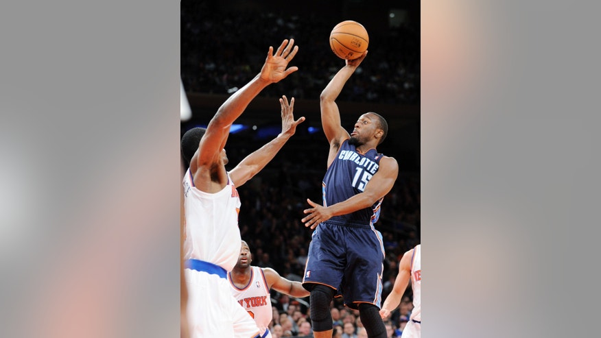Charlotte Bobcats' Kemba Walker, right, puts up a shot over New York Knicks' Metta World Peace during the fourth quarter of an NBA basketball game Tuesday, Nov. 5, 2013, at Madison Square Garden in New York. The Bobcats defeated the Knicks 102-97. (AP Photo/Bill Kostroun)