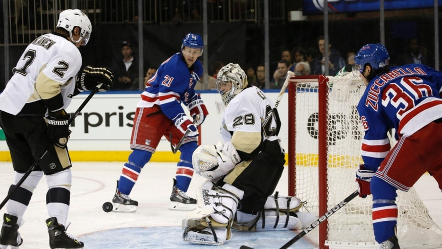 Pittsburgh Penguins goalie Marc-Andre Fleury (29) makes a save in the second period of an NHL hockey game, as defenseman Matt Niskanen (2) and New York Rangers center Derek Stepan (21) and right wing Mats Zuccarello (36) watch on Wednesday, Nov. 6, 2013, in New York. (AP Photo/Kathy Willens)