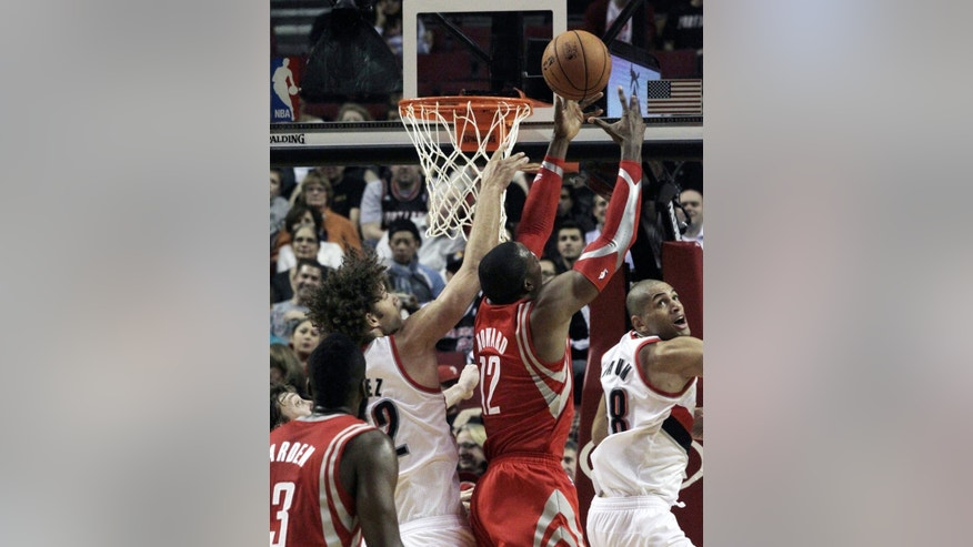 Houston Rockets forward Dwight Howard, second from right, pulls in a rebound against Portland Trail Blazers' Robin Lopez, left, and Nicolas Batum, from France, during the first half of an NBA basketball game in Portland, Ore., Tuesday, Nov. 5, 2013. (AP Photo/Don Ryan)