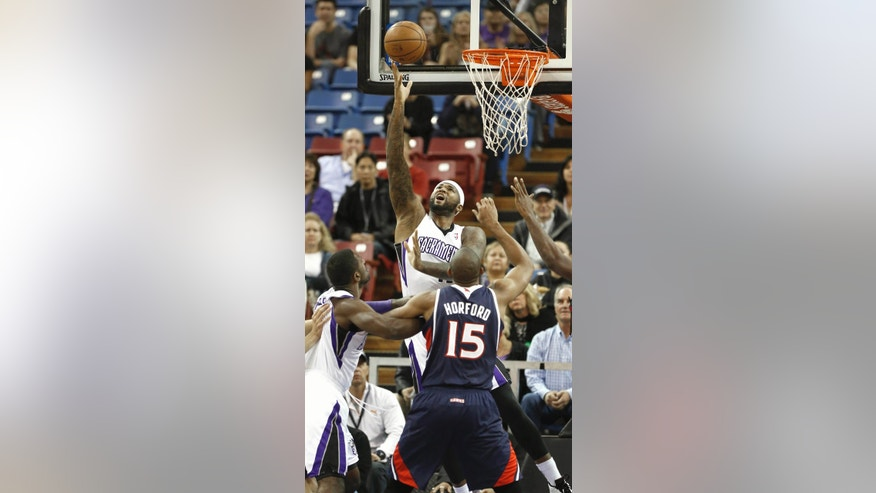 Sacramento Kings center DeMarcus Cousins, center, shoots over Atlanta Hawks center Al Horford (15) as Kings forward Patrick Patterson, left, watches during the first quarter of an NBA basketball game in Sacramento, Calif., Tuesday, Nov. 5, 2013.(AP Photo/Rich Pedroncelli)