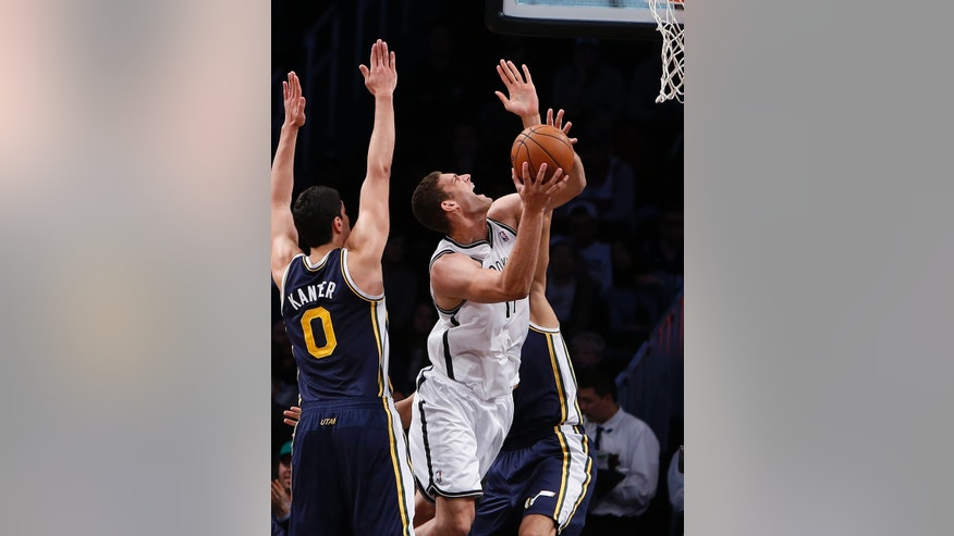 Brooklyn Nets' Brook Lopez, center, shoots against Utah Jazz's Enes Kanter (0) and Rudy Gobert, rear, during the second half of an NBA basketball game Tuesday, Nov. 5, 2013, in New York. Brooklyn won 104-88. (AP Photo/Jason DeCrow)