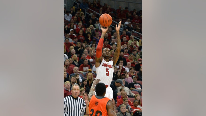 Louisville's Kevin Ware puts up a shot over the defense of Pikeville's John Nunnaly during the second half of an NCAA college basketball exhibition game, Wednesday, Nov. 6, 2013, in Louisville, Ky. Louisville defeated Pikeville 90-61. (AP Photo/Timothy D. Easley)