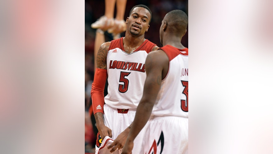 Louisville's Kevin Ware, left, talks to teammate Chris Jones during the second half of an NCAA college basketball exhibition game, Wednesday, Nov. 6, 2013, in Louisville, Ky. This is Ware's first game back since breaking his leg in an NCAA tournament game in March. (AP Photo/Timothy D. Easley)