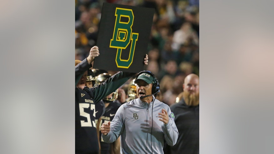FILe - In this Oct. 5, 2013 file photo, Baylor head football coach Art Briles checks on a play against West Virginia during the first half of an NCAA college football game in Waco, Texas.  No. 5 Baylor takes on No. 12 Oklahoma in Waco on Thursday, Nov. 7, 2013.  (AP Photo/Rod Aydelotte, File)