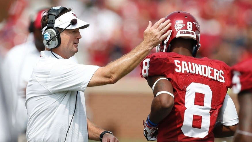 FILe - In this Sept. 14, 2013 file photo, Oklahoma head coach Bob Stoops, left, greets wide receiver Jalen Saunders (8) after Saunders scored a touchdown against Tulsa in the fourth quarter of an NCAA college football game in Norman, Okla. No. 5 Baylor and No. 12 Oklahoma meet Thursday, Nov. 7, 2013 in Waco, Texas. (AP Photo/Sue Ogrocki, File)
