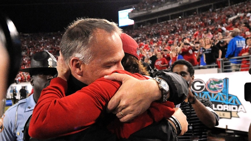 Georgia head coach Mark Richt hugs his wife Katharyn after their 23-20 win over Florida in an NCAA football game, Saturday, Nov. 2, 2013, in Jacksonville, Fla. (AP Photo/Stephen Morton)