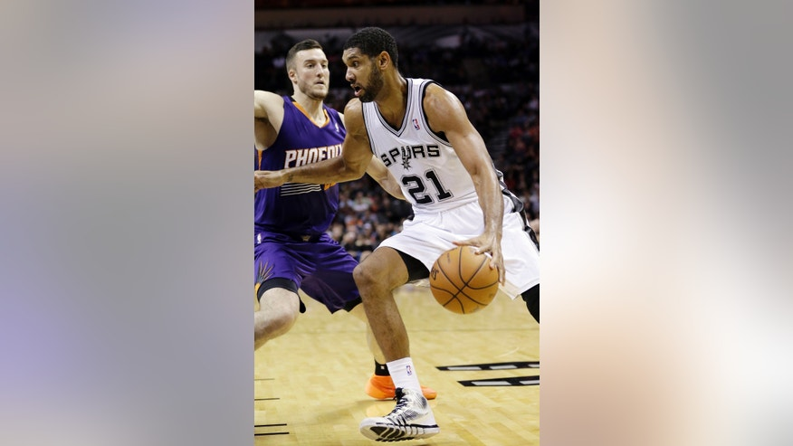 San Antonio Spurs' Tim Duncan (21) works the ball around Phoenix Suns' Miles Plumlee during the first half of an NBA basketball game Wednesday, Nov. 6, 2013, in San Antonio. (AP Photo/Eric Gay)