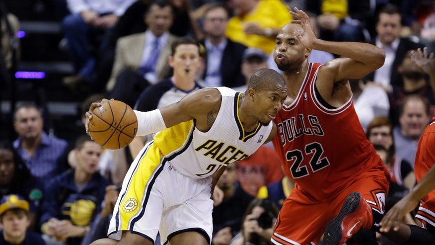 Chicago Bulls forward Taj Gibson, right, defends Indiana Pacers forward David West as he drives to the basket in the first half of an NBA basketball game in Indianapolis, Wednesday, Nov. 6, 2013.  (AP Photo/Michael Conroy)