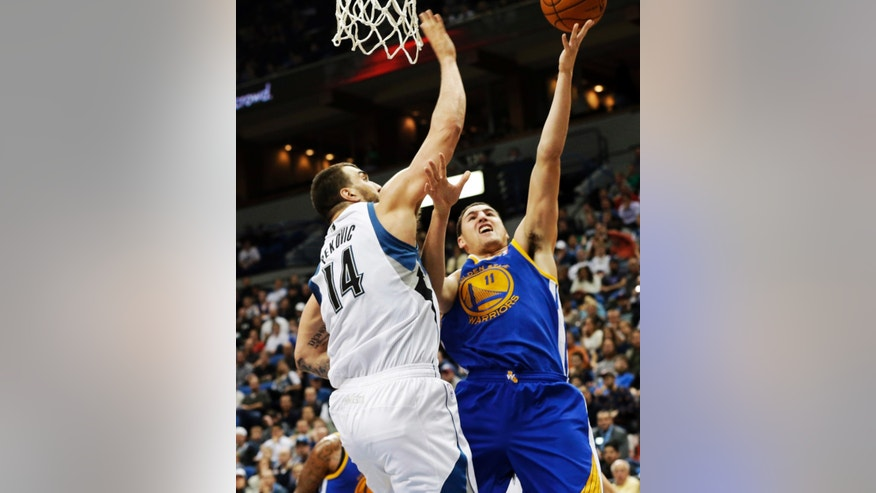 Golden State Warriors' Klay Thompson, right, shoots as Minnesota Timberwolves' Nikola Pekovic, of Montenegro, defends in the second half of an NBA basketball game Wednesday, Nov. 6, 2013, in Minneapolis. Thompson led the Warriors with 30 points in their 106-93 win. (AP Photo/Jim Mone)