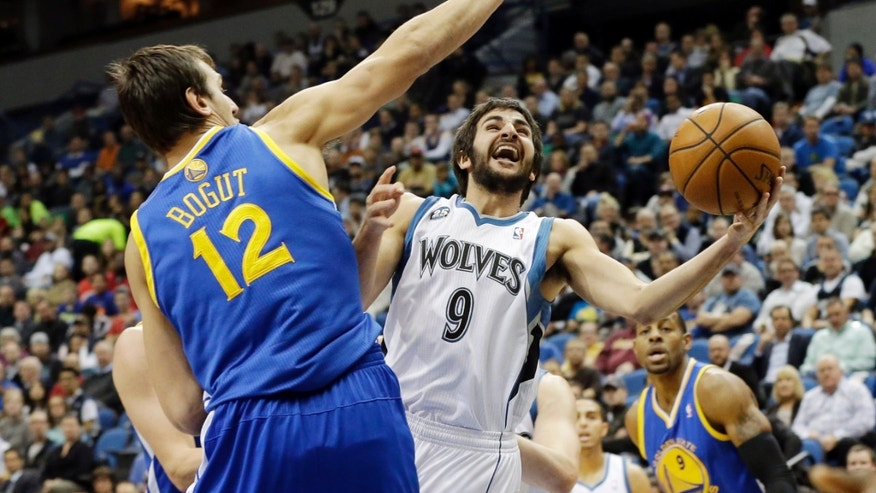 Minnesota Timberwolves' Ricky Rubio, right, of Spain, lays up as Golden State Warriors' Andrew Bogut, left, of Australia, defends in the first quarter of an NBA basketball game Wednesday, Nov. 6, 2013, in Minneapolis. (AP Photo/Jim Mone)