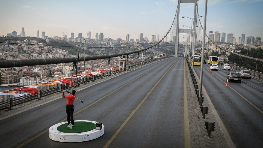 Nov. 5, 2013: Golf star Tiger Woods of the United States makes a shot from East to West on the iconic Bosporus Bridge that separates the continents of Europe and Asia, in Istanbul, Turkey.