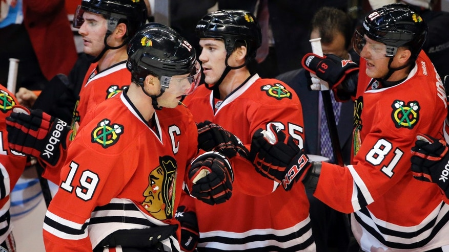 Chicago Blackhawks' Jonathan Toews (19) celebrates with teammates after he scored a goal during the first period of an NHL hockey game against the Winnipeg Jets in Chicago, Wednesday, Nov. 6, 2013. (AP Photo/Nam Y. Huh)