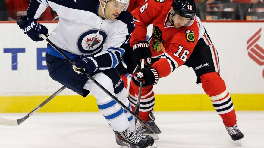 Winnipeg Jets' Eric Tangradi (27) controls the puck against Chicago Blackhawks' Marcus Kruger (16) during the first period of an NHL hockey game in Chicago, Wednesday, Nov. 6, 2013. (AP Photo/Nam Y. Huh)