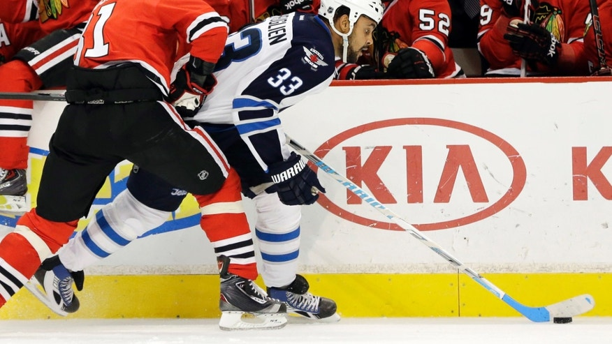 Winnipeg Jets' Dustin Byfuglien (33) controls the puck against Chicago Blackhawks' Marian Hossa during the first period of an NHL hockey game in Chicago, Wednesday, Nov. 6, 2013. (AP Photo/Nam Y. Huh)
