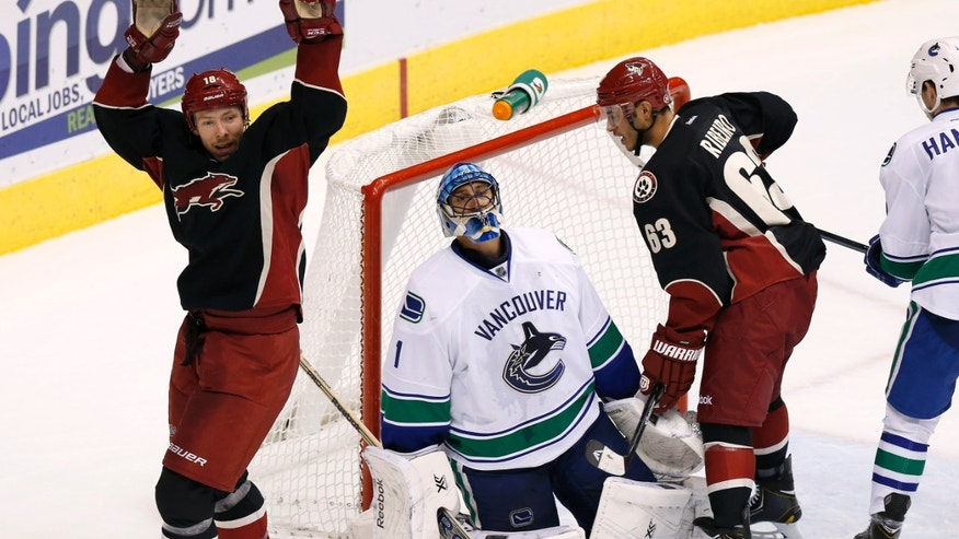 Phoenix Coyotes' David Moss, left, and Mike Ribeiro (63) celebrate a goal by teammate Shane Doan, as Vancouver Canucks' Roberto Luongo (1) kneels dejectedly on the ice during the second period of an NHL hockey game on Tuesday, Nov. 5, 2013, in Glendale, Ariz. (AP Photo/Ross D. Franklin)
